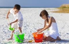 children, boy, girl, brother & sister playing on beach - stock photo