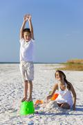 Children, boy, girl, brother & sister playing on beach Stock Photos