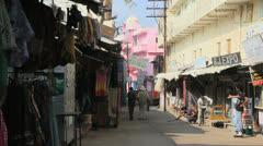 India Rajasthan Pushkar pink building at end of vendor row  Stock Footage