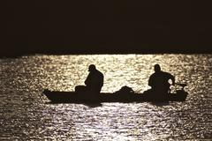 Silhouette of Canoe on Lake - stock photo