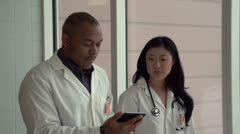 Two doctors walking and talking with their tablet - stock footage