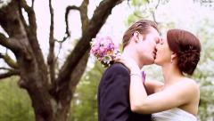 Affectionate bride and groom kissing on their wedding day - stock footage