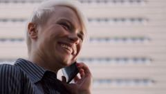 Telecommunications, businesswoman standing near office, talking on cell phone - stock footage