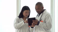Doctors looking over a chart on tablet with a serious expression Stock Footage