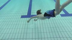 child dives in a pool and gets a ring - stock footage