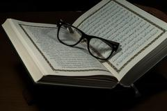 Pages of holy koran and geek glasses Stock Photos