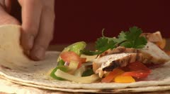Rolling up a tortilla filled with chicken breast and salsa - stock footage