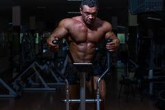 male bodybuilder using the elliptical machine - stock photo