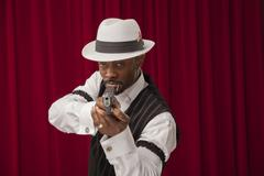 Stock Photo of African American wearing a retro mobster suit with a gun