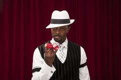 African American gambler in retro suit holding dice Stock Photos