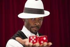 African American gambler wearing retro suit holding oversize dice - stock photo