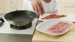 Rashers of bacon being placed in a pan Stock Footage