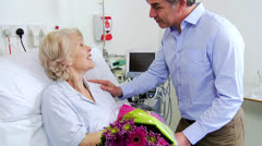 Senior Patient Being Visited by Son With Flowers Stock Footage