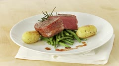 Beef fillet wrapped in bacon (fillet mignon) with beans and potatoes Stock Footage