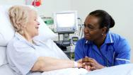 Stock Video Footage of Caring Nurse Reassuring Older Patient Hospital Bed