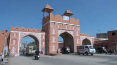 India Rajasthan Jaipur traffic moves through pink gate 2 Stock Footage