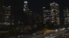 Pan right of highway traffic in downtown Los Angeles by night, LA, California - stock footage