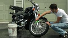 Man washing motorcycle in driveway with chamois front ms Stock Footage