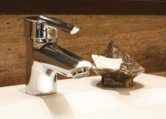 faucet with soap in coconut shell - stock photo