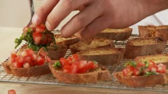 Baguette slices being topped with a tomato and basil mixture Stock Footage
