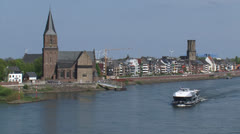 Skyline Emmerich, Germany + tourist boat cruising river Rhine Stock Footage