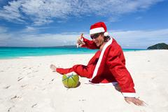 Stock Photo of santa claus on beach relaxing