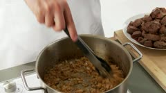 Onion and garlic being fried and pieces of meat being stirred in Stock Footage