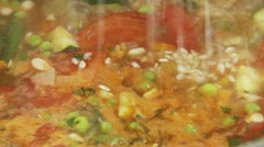 Risotto rice being added to minestrone and being seasoned with pepper Stock Footage
