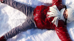 Girl makes a snow angel Stock Footage