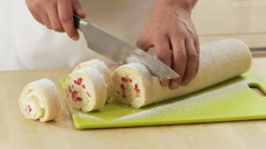 Strawberry cream swiss roll being sliced Stock Footage