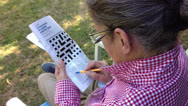 Stock Video Footage of Grandmother doing crossword outdoors - 1080p