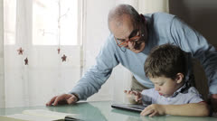 Grandfather and grandson using digital tablet together - stock footage