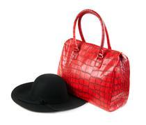 Red fashion ladies handbag and a black felt hat Stock Photos