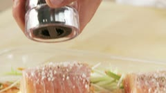 Salmon fillets being seasoned with pepper Stock Footage