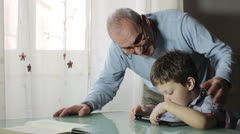 Child playing with a video game together his grandfather Stock Footage