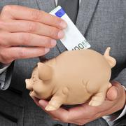 Man in suit introducing a euro bill in a piggy bank Stock Photos