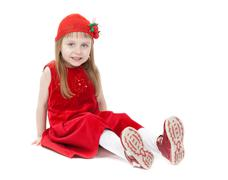 a girl aged four years in a red dress sitting on the floor - stock photo
