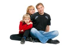Happy family sitting in the lotus position Stock Photos