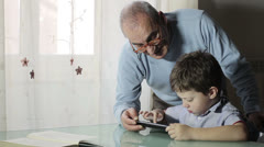 Child using tablet with his grandfather - touching tablet Stock Footage