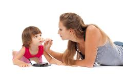 young mother paints lipstick little daughter in the studio - stock photo