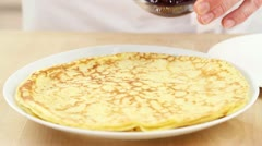 Crepes being spread with jam Stock Footage