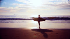 Doly shot of Silhouetted surfer girl Stock Footage