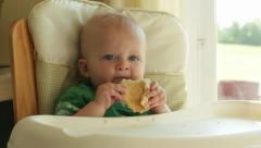 1 year old caucasian male baby eating pancake in highchair Stock Footage