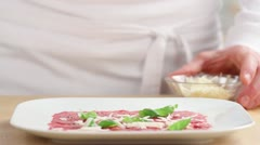 Beef carpaccio being sprinkled with freshly grated parmesan Stock Footage