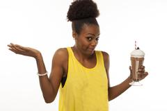 Stock Photo of African American woman trying to make a healthy decision about her milkshake