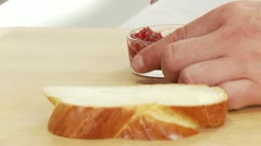 A slice of sweet bread being spread with jam Stock Footage