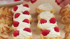 Profiteroles being filled with cream and raspberries Stock Footage