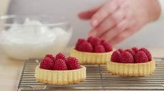 Meringue being spread onto raspberry tartlets Stock Footage