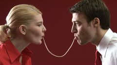 Man and woman eating the same strand of spaghetti Stock Footage