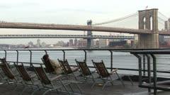 Brooklyn Bridge, man in deck chair at Pier 17 Stock Footage